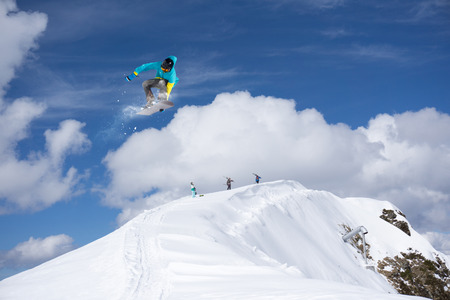 snowboard: Flying snowboarder on mountains. Extreme winter sport.