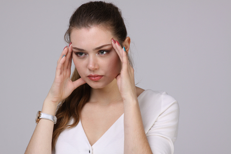 dolor de cabeza: Beautiful young woman with headache touching her temples, on grey background
