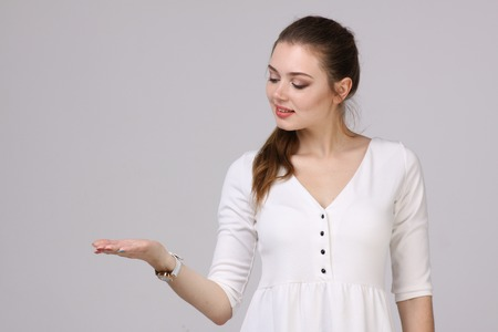 open space: Woman showing a product. Empty copy space on the open hand palm, over grey background.
