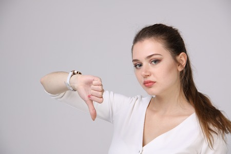 rejection sad: woman in white dress showing thumb down Stock Photo
