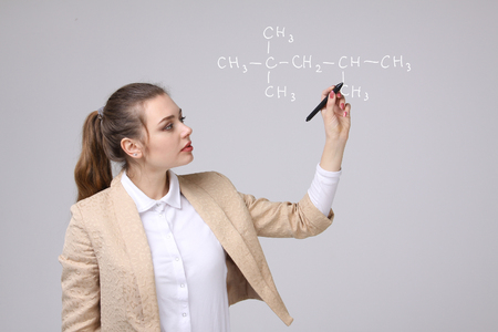 Woman chemist shows a molecular structure, on gray background Stock Photo