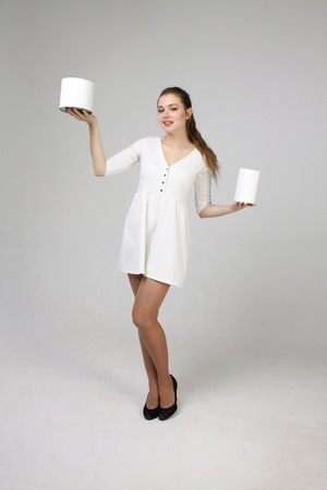 paint cans: Young woman in white dress holding paint cans Stock Photo