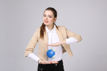 scientist woman: Young woman scientist with model of water molecule, on gray background.