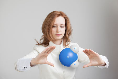 Young woman scientist with model of water molecule, on gray background.