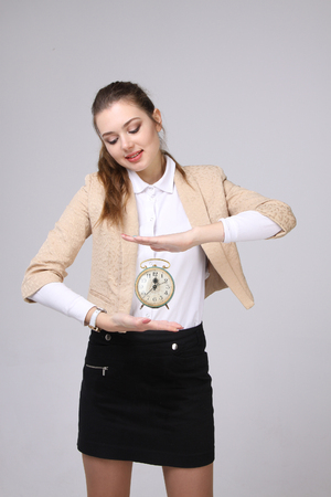 attractive  female: Young attractive woman showing clock, on gray background