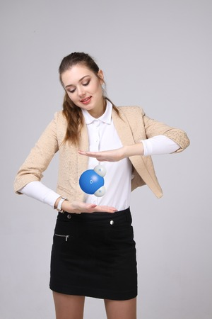 water molecule: Young woman scientist with model of water molecule, on gray background.