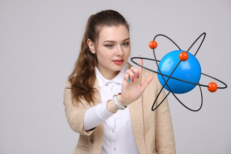 atomic structure: Woman scientist with atom model on grey background, research concept