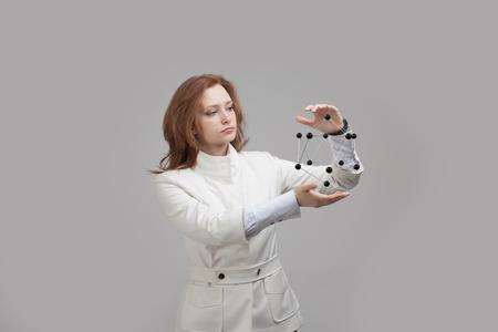 molecula: mujer joven científico modelo de la molécula o red cristalina que sostiene.