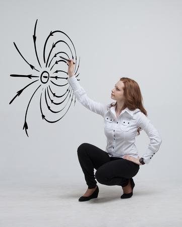 Junge Frau, zieht Physiklehrer ein Diagramm des elektrischen Feldes, auf grauem Hintergrund Standard-Bild