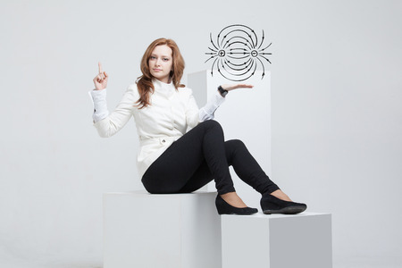 dipole: Young woman, physics teacher showing a diagram of the electric field, on gray background Stock Photo
