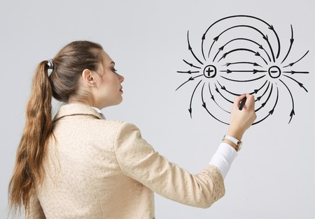 Young woman, physics teacher draws a diagram of the electric field, on gray background