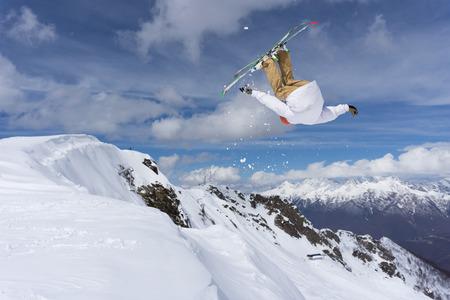 rider salto con gli sci sulle montagne. Sport estremo di sci freeride.