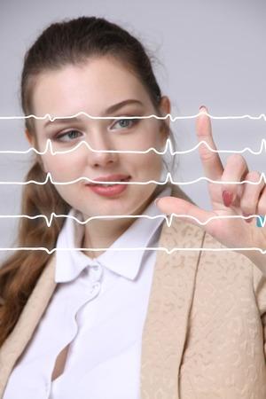 electrocardiograma: médico de la mujer joven que trabaja con el cardiograma. líneas de electrocardiograma en el aire