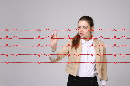 elettrocardiogramma: Young doctor woman working with cardiogram. Electrocardiogram lines in air Archivio Fotografico