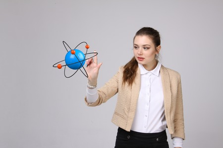 Woman scientist with atom model on grey background, research concept