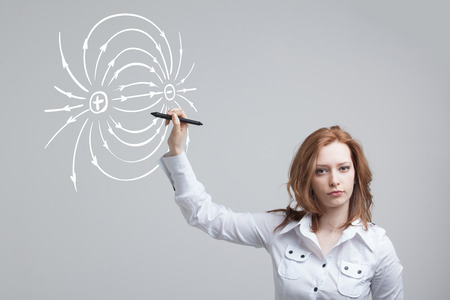 stylus: Young woman, physics teacher draws a diagram of the electric field, on gray background
