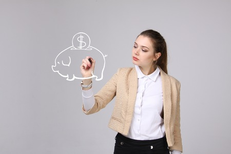 writing on screen: young businesswoman, woman drawing a piggy Bank Stock Photo