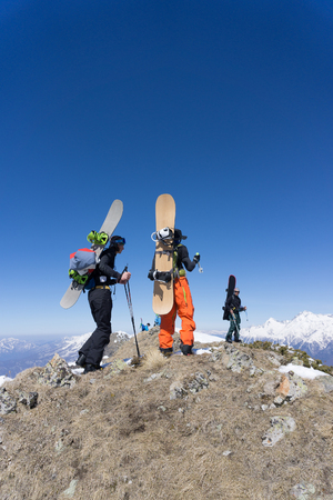 mountaineering: Snowboarders walking uphill for freeride, extreme winter mountaineering sport