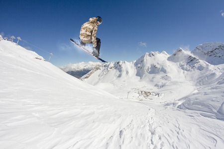 freeride: Snowboard rider jumping on snowy mountains. Extreme snowboard freeride sport.