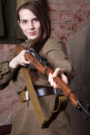 antique rifle: Young woman in Russian military uniform shoots a rifle. Female soldier during the second world war.
