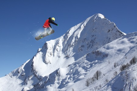 snowy mountains: Snowboard rider jumping on snowy mountains. Extreme snowboard freeride sport.