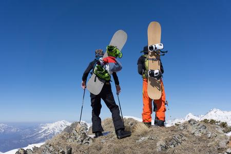 freeride: Snowboarders walking uphill for freeride, extreme winter mountaineering sport