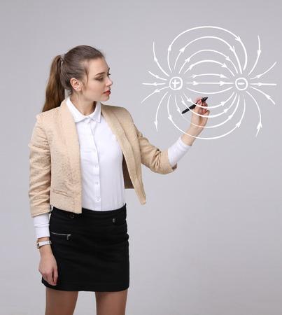 Junge Frau, zieht Physiklehrer ein Diagramm des elektrischen Feldes, auf grauem Hintergrund