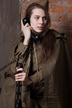 speaks: Young woman in Russian military uniform speaks on the phone. Female soldier during the second world war.