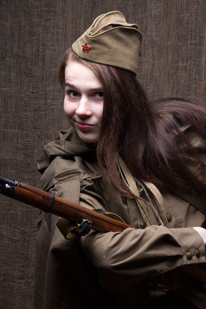 Young woman in Russian military uniform with rifle. Female soldier during the second world war.