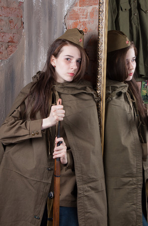 the caucasian beauty: Young woman in Russian military uniform with rifle. Female soldier during the second world war.