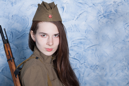 antique rifle: Young woman in Russian military uniform with rifle. Female soldier during the second world war.