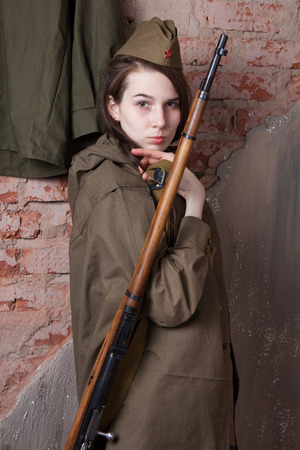 weaponry: Young woman in Russian military uniform with rifle. Female soldier during the second world war.