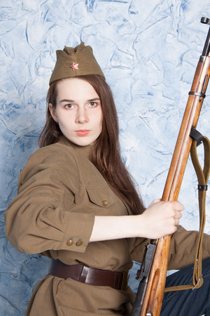 vintage military rifle: Young woman in Russian military uniform with rifle. Female soldier during the second world war.