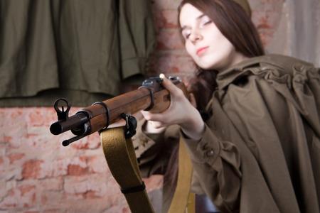 seconda guerra mondiale: Giovane donna in uniforme militare russo spara un fucile. Soldato femminile durante la seconda guerra mondiale.