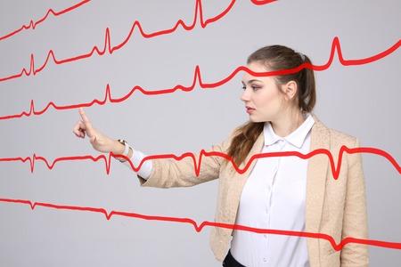 electrocardiograma: m�dico de la mujer joven que trabaja con el cardiograma. l�neas de electrocardiograma en el aire