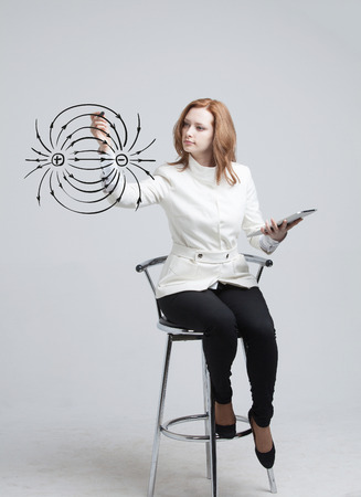dipole: Young woman, physics teacher draws a diagram of the electric field, on gray background