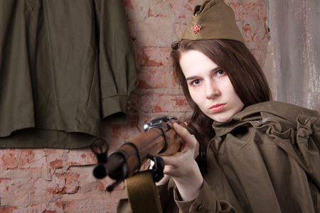 weaponry: Young woman in Russian military uniform shoots a rifle. Female soldier during the second world war.