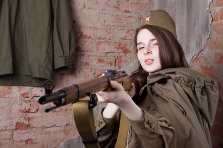 Young woman in Russian military uniform shoots a rifle. Female soldier during the second world war.