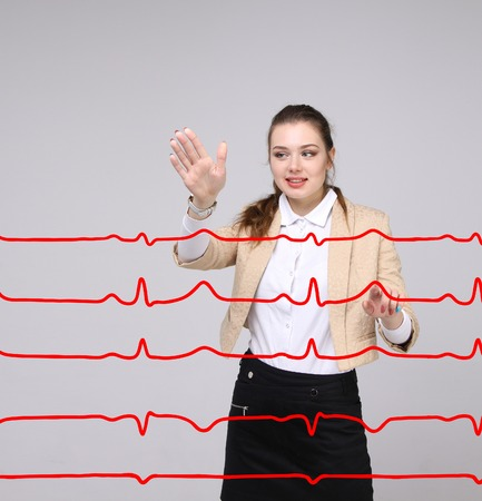 of electrocardiogram: Young doctor woman working with cardiogram. Electrocardiogram lines in air Stock Photo