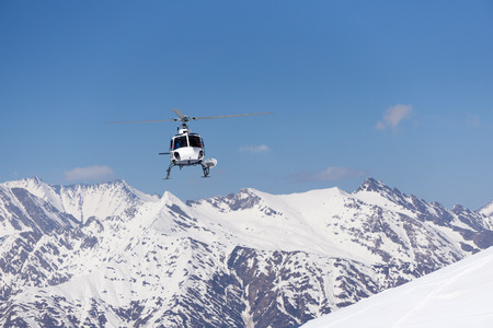 heli: White rescue helicopter in the snowy mountains
