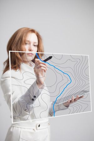 geographic: Geographic information systems concept, woman scientist working with futuristic interface in GIS software on a transparent screen.