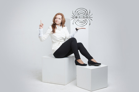 electromagnetic field: Young woman, physics teacher showing a diagram of the electric field, on gray background Stock Photo