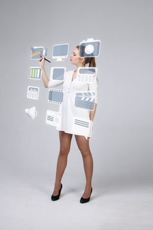 holography: Young woman pressing multimedia and entertainment icons on a virtual background
