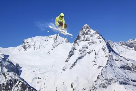 freeride: Ski rider jumping on snowy mountains. Extreme ski freeride sport.