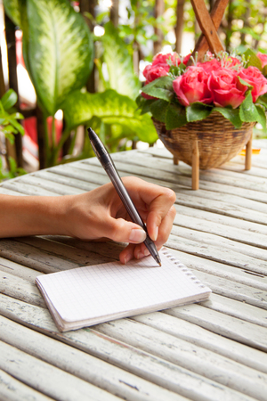 novelist: Female hand writing in a notebook on wooden table in summer cafe