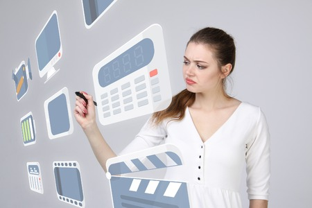 entertainment background: Young woman pressing multimedia and entertainment icons on a virtual background