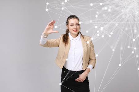 linked services: Worldwide network or wireless internet connection futuristic concept. Young woman working with linked dots on grey background. Stock Photo
