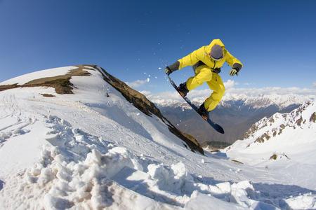 눈 덮인 산에 점프 스노우 보드 라이더. 익스트림 스노우 보드 프리 라이드 스포츠입니다. 스톡 콘텐츠