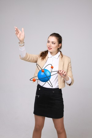 corpuscle: Woman scientist with structure atom model on grey background, research concept