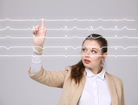 electrocardiogram: Young doctor woman working with cardiogram. Electrocardiogram lines in air Stock Photo